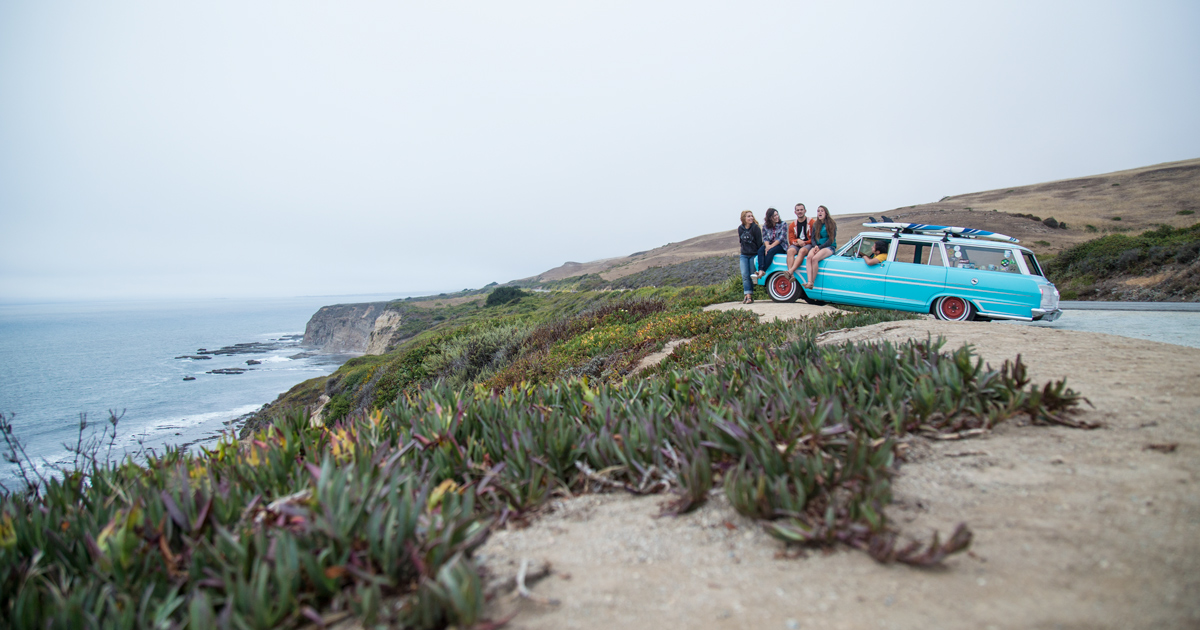 Young people sitting on teal car near ocean
